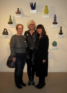 """Women Working in Clay"" Opening with Gail Holmberg, Linda Hillman and Joan Friedberger in front of Virginia Scotchie's ceramic wall installation."
